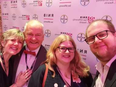 A group selfie in front of the same banner. On the left an older couple, the woman rests her hand palm flat on the mans chest. He wears a red bow tie, they both have big smiles. In the middle Amy