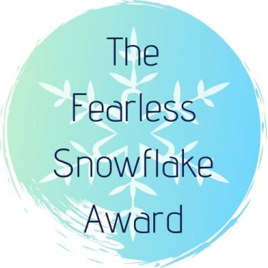 The Fearless Snowflake Award Logo. A blue softly painted background with the light outline of a white snowflake. It reads The Fearless Snowflake Award
