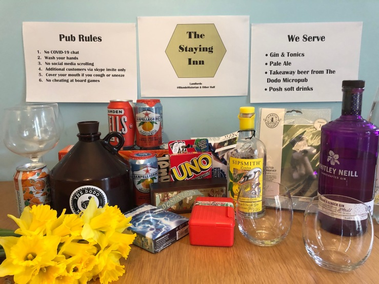 A table filled with drinks, bottles, a bunch of daffodils, glasses and board games. On the blue wall behind The Staying Inn sign a menu and the rules