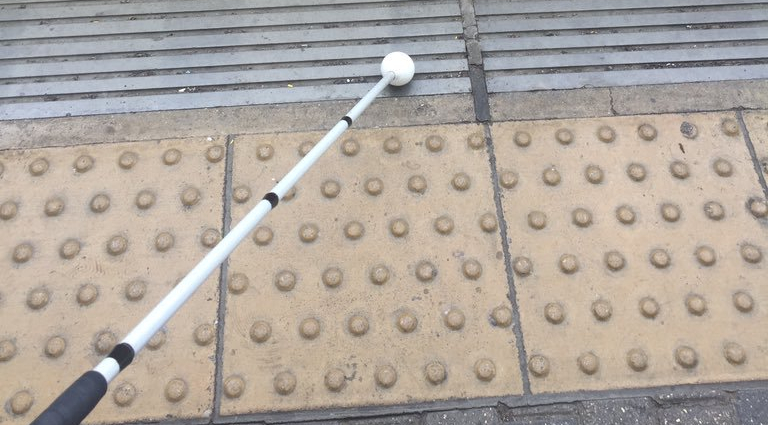 Amy's long white cane reaches out diagonally from the right hand corner of the photo. It reaches across tactile paving.